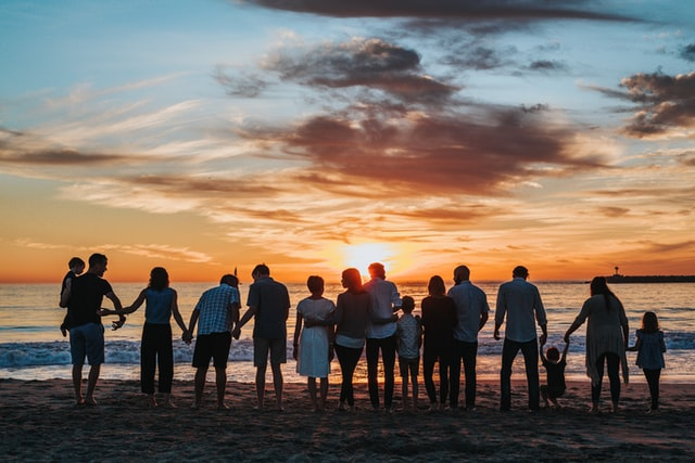 Large family gathered on a beach for a reunion overlooking the water at sunset