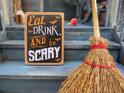 Broom and sign that says eat drink and be scary