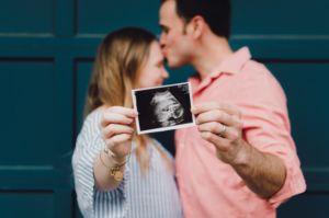 Pregnant couple joyfully holding up a photo of a sonogram