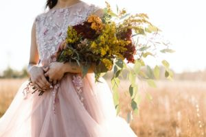 Bride standing in a field holding a fall wedding bouquet