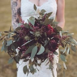 bride with tattoo holding unique wedding bouquet